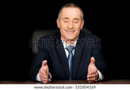 Smiling businessman sitting at desk. - stock photo