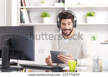Smiling businessman sitting at desk in front of computer and listening music at office while working. Young professional holding in his hand digital tablet and downloading music. - stock photo