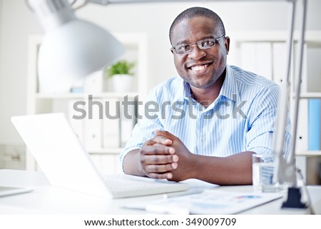Smiling businessman sitting at his table at office - stock photo