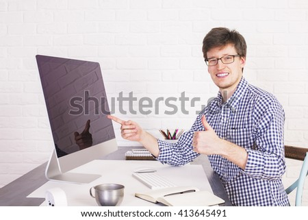 Smiling businessman sitting at office desk with large computer screen, pointing at it and showing thumbs up on white brick background. Mock up - stock photo