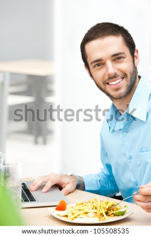 Smiling businessman sitting at the table and having lunch - stock photo