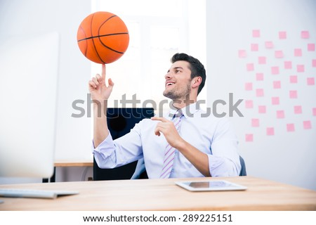 Smiling businessman sitting at the table and spining ball in office - stock photo