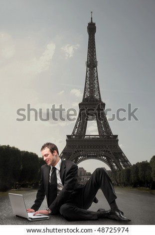 Smiling businessman sitting in front of the Eiffel Tower and working with a laptop - stock photo