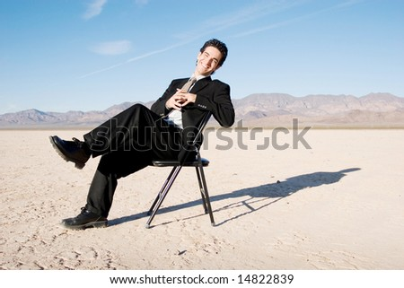 Smiling businessman sitting on a chair - stock photo