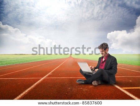 Smiling businessman sitting on a running track and using a laptop - stock photo