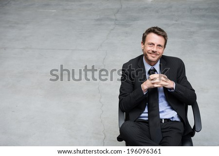Smiling businessman sitting on office chair with hands clasped on concrete floor background. - stock photo