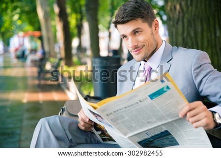 Smiling businessman sitting on the bench with newspaper and looking at away in park - stock photo