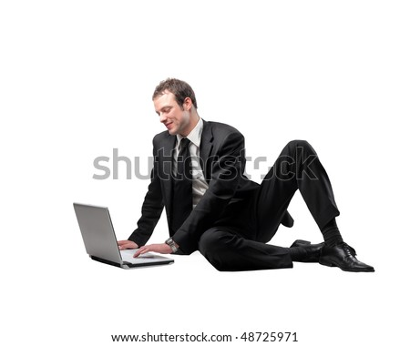 Smiling businessman sitting with a laptop in front of him - stock photo