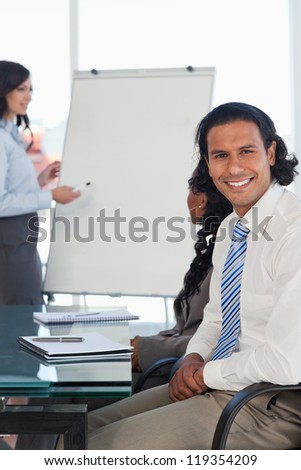 Smiling businessman sitting with hands crossed while listening to a presentation - stock photo
