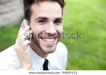 Smiling businessman speaking by phone - stock photo