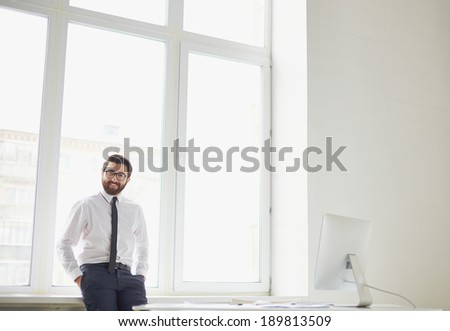 Smiling businessman standing by the window in office - stock photo