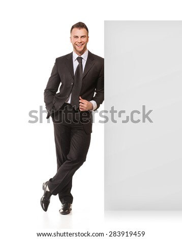 Smiling businessman standing near board isolated on white background
