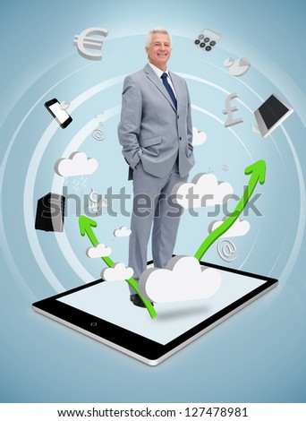 Smiling businessman standing on a digital tablet pc - stock photo