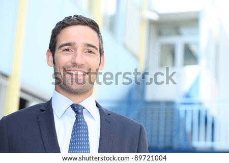 Smiling businessman standing outside a building on a sunny day - stock photo
