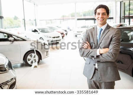 Smiling businessman standing with arms crossed at new car showroom - stock photo