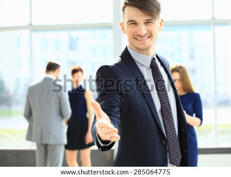 Smiling businessman stretching his hand out for a handshake in foreground and his coworkers discussing business - stock photo