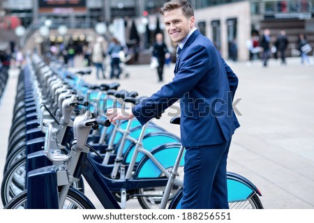Smiling businessman take his bicycle from parking - stock photo