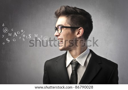 Smiling businessman talking and symbols coming out of his mouth - stock photo