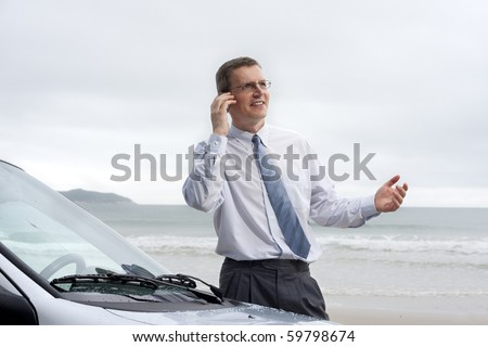 Smiling businessman talking on cell phone by his car on a beach - stock photo