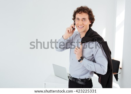 Smiling businessman talking on the phone in office - stock photo