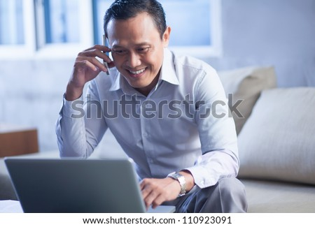 Smiling businessman using a mobile phone and looking at laptop - stock photo