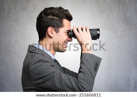 Smiling businessman using binoculars - stock photo