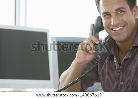 Smiling businessman using landline phone in office - stock photo