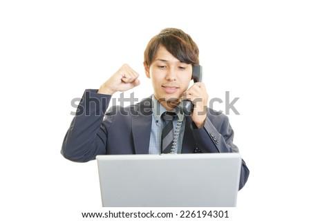 Smiling businessman using laptop - stock photo