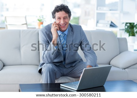 Smiling businessman using laptop and mobile phone in living room - stock photo