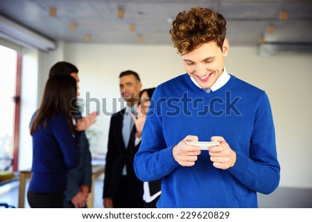 Smiling businessman using smartphone in front of a colleagues - stock photo