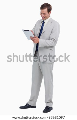 Smiling businessman using tablet computer against a white background - stock photo