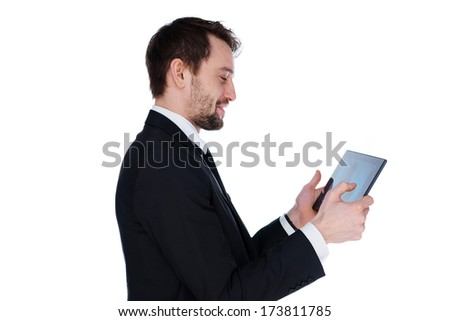 Smiling businessman with a beard standing sideways looking at his tablet computer screen isolated on white - stock photo