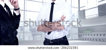 Smiling businessman with arms crossed against airport terminal - stock photo