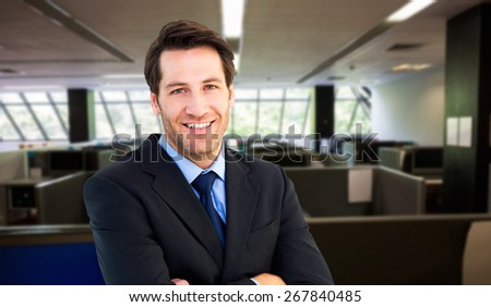 Smiling businessman with arms crossed against empty office with separate units - stock photo