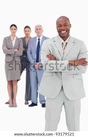 Smiling businessman with arms folded and team behind him against a white background - stock photo