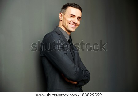 Smiling businessman with arms folded standing on gray background - stock photo