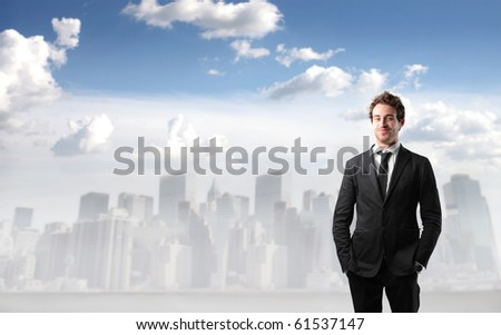 Smiling businessman with cityscape on the background - stock photo