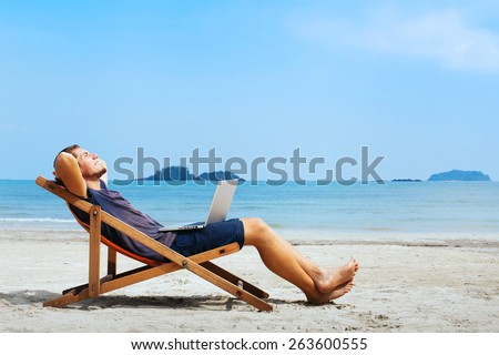smiling businessman with computer relaxing on the beach - stock photo