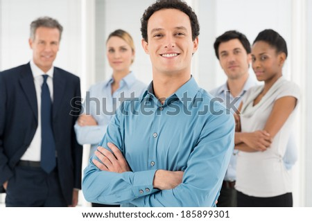 Smiling Businessman With Crossed Arms In Front Of Coworker - stock photo