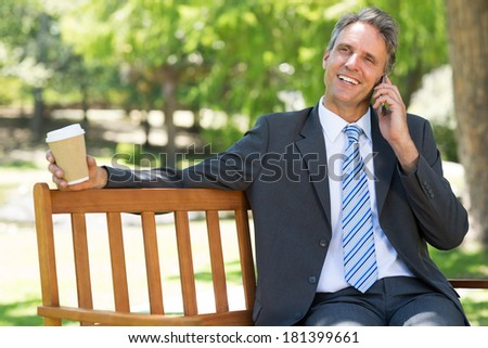 Smiling businessman with disposable cup answering cellphone on park bench - stock photo