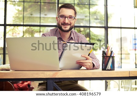 Smiling businessman with glasses looking at camera and taking notes in his home office - stock photo