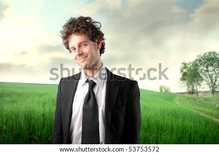 Smiling businessman with green meadow on the background - stock photo
