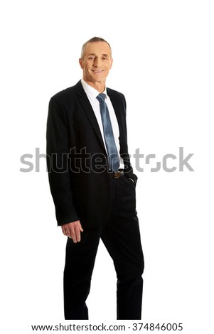 Smiling businessman with hand in pocket - stock photo