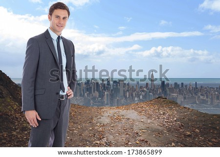 Smiling businessman with hand on hip against large city on the horizon - stock photo