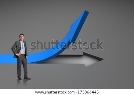 Smiling businessman with hand on hip against red arrow pointing up