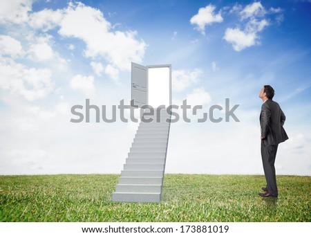 Smiling businessman with hands on hips against open door at top of stairs in a field