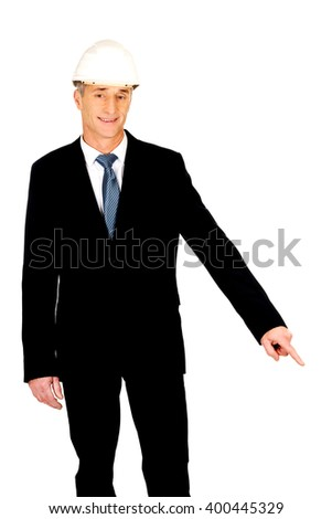 Smiling businessman with hard hat pointing down - stock photo
