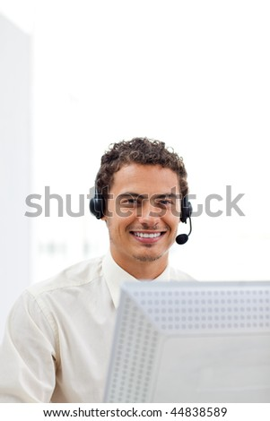 Smiling businessman with headset on working at a computer - stock photo