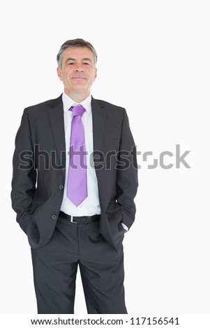 Smiling businessman with his hands in his pockets