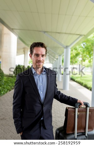 Smiling businessman with luggage standing at the station